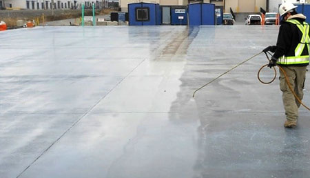 Worker spraying solution on concrete